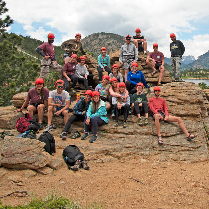 A large group of rock climbers pose on rock outcropping in Estes Park, Colorado.