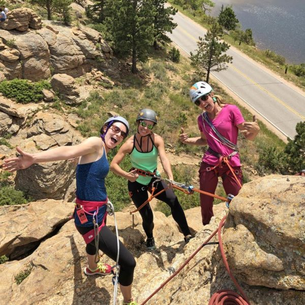 A group of women from a mountaineering club have fun rock climbing near Denver, Colorado.