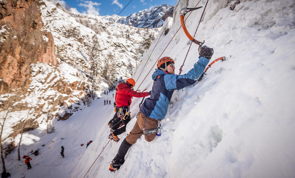 An ice climber swings his tool into the ice on an ice climbing adventure fundraiser with Paradox Sports.