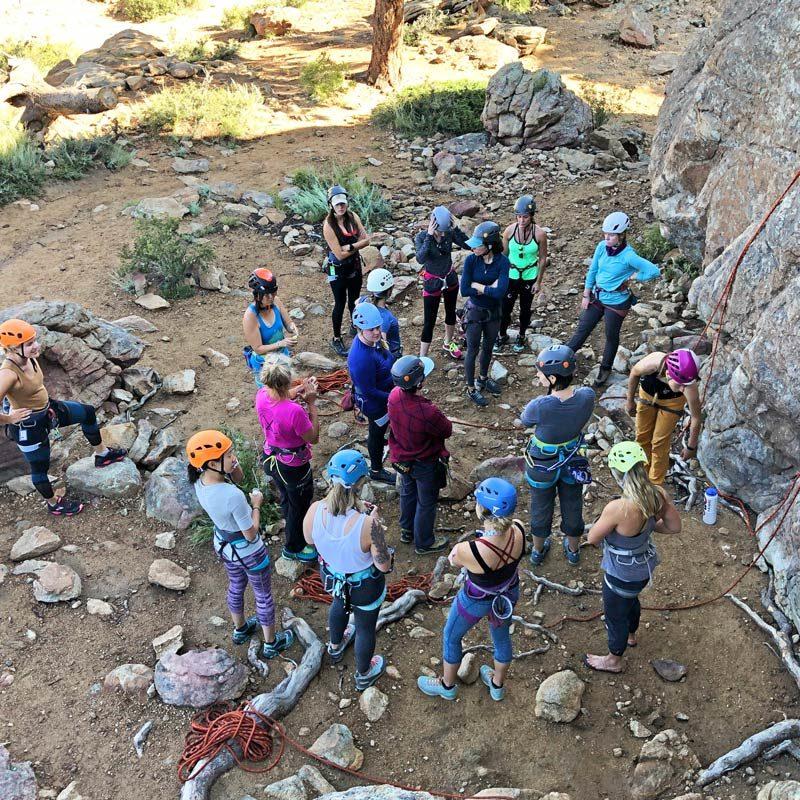 A corporate group prepares for an outdoor rock climbing activity near Denver, Colorado.