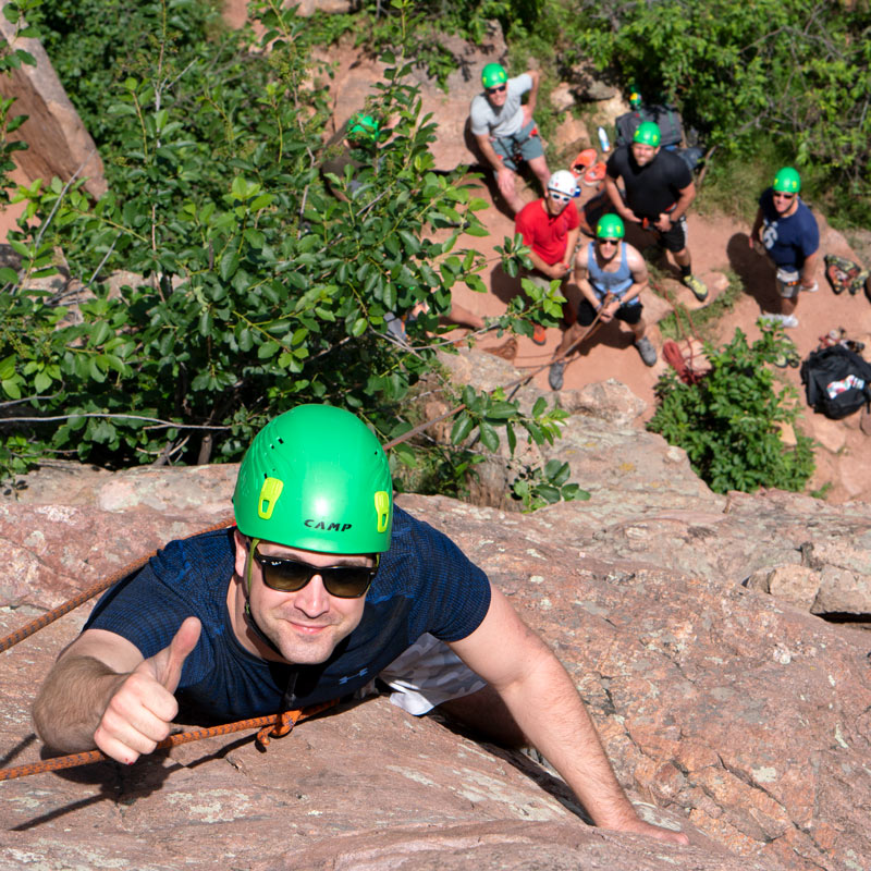 A climber celebrates reaching the top of an outdoor rock climb during a corporate team activity.