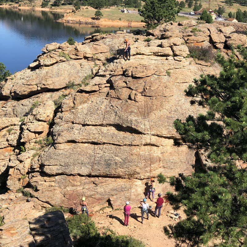 A climber ascends a rock face during a corporate team building activity near Denver, Colorado.