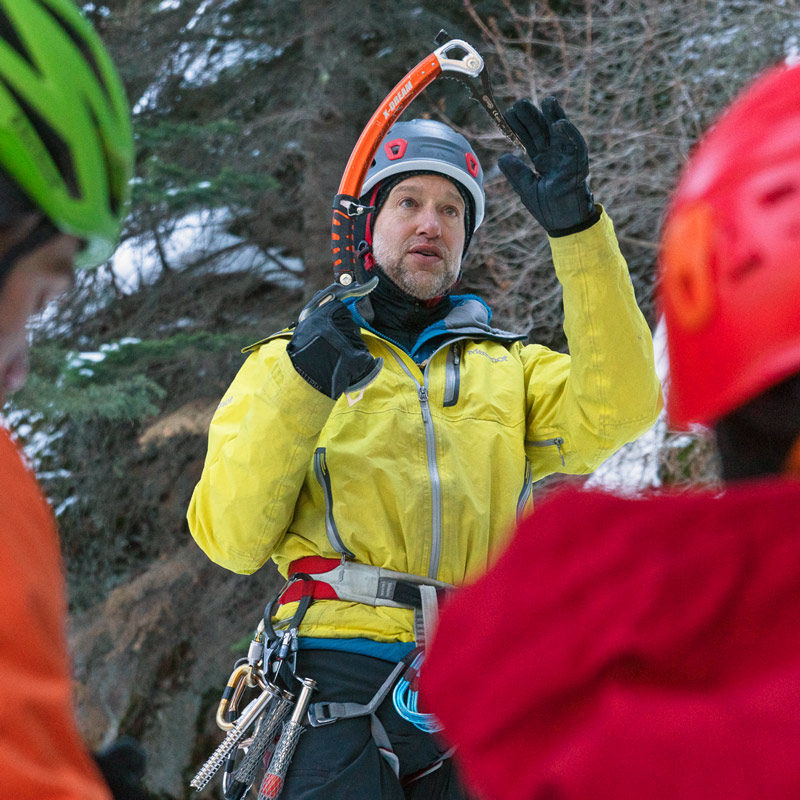 An instructor on an ice climbing course teaches a lesson about ice tools and how to use them properly to climb ice.