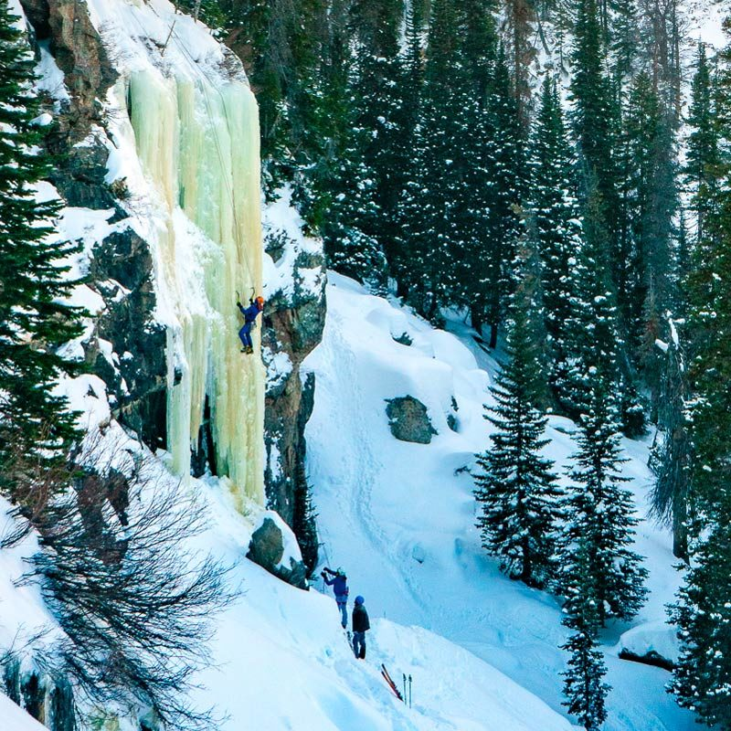 An ice climber swings a tool into a frozen waterfall during an ice climbing lesson in Rocky Mountain National Park, Colorado.