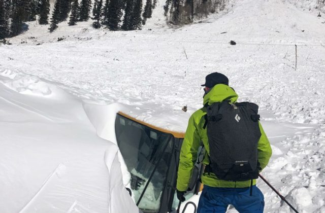 Colorado Mountain School Guide, Jason Maurer, inspects a piece of equipment that had been buried by avalanche debris at Mosquito Gulch, Colorado.