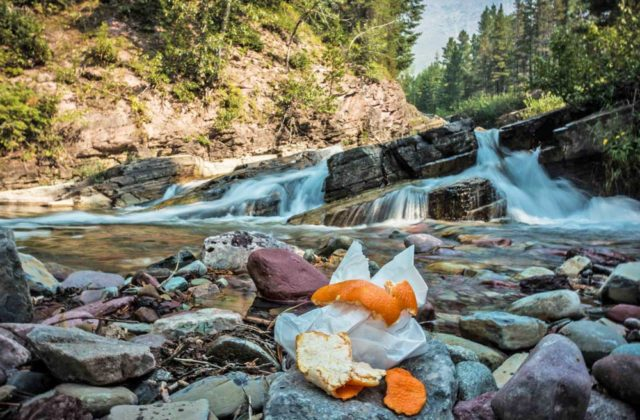 A small pile of garbage sits on a rock near an otherwise pristine stream and waterfall.