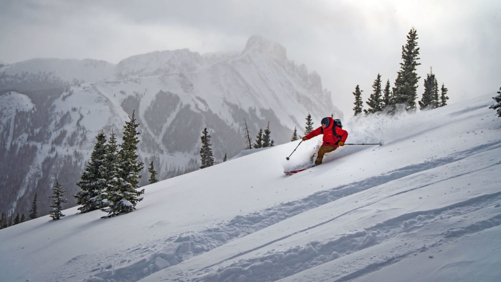 A backcountry skier carves a turn in powder in backcountry of Cameron Pass, Colorado.