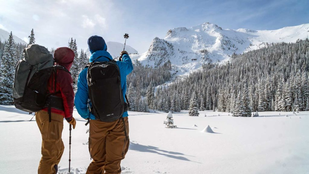 A pair of backcountry skiers look at the steep terrain on Cameron Pass.