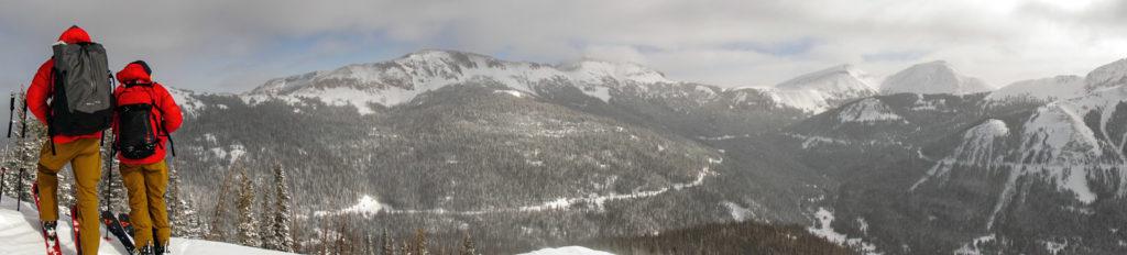 Two backcountry skiing guides overlook mountainous terrain on Cameron Pass in Colorado.