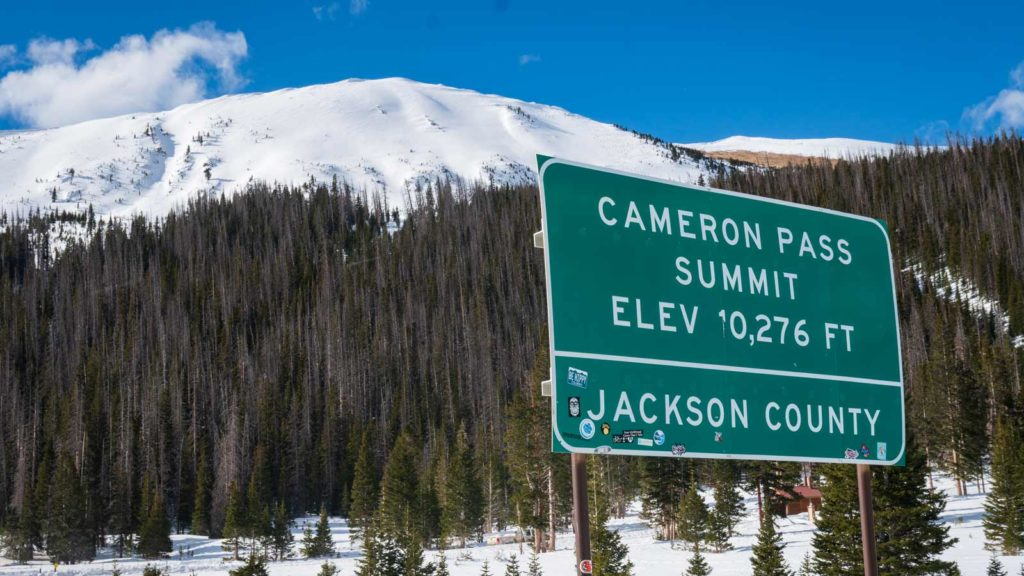"""A sign with snowy peaks in the background reads """"Cameron Pass Summit Elevation 10,276""""."""