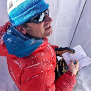 Colorado Mountain School Guide, Matt Hartman, takes snow observation notes in his AIARE booklet during a snow pit analysis.