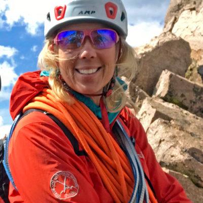 Colorado Mountain School Guide, Mia Tucholke, smiles for the camera on a guided rock climb.