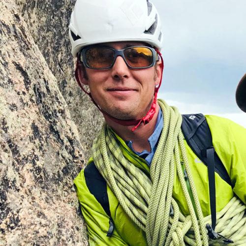 Colorado Mountain School Guide, Adam Baxter, smiles for the camera high on an alpine rock climb in Rocky Mountain National Park.