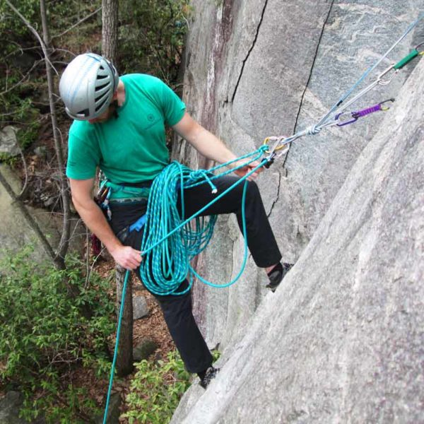 A rock guide looks down to his follower as he belays from a trad anchor.