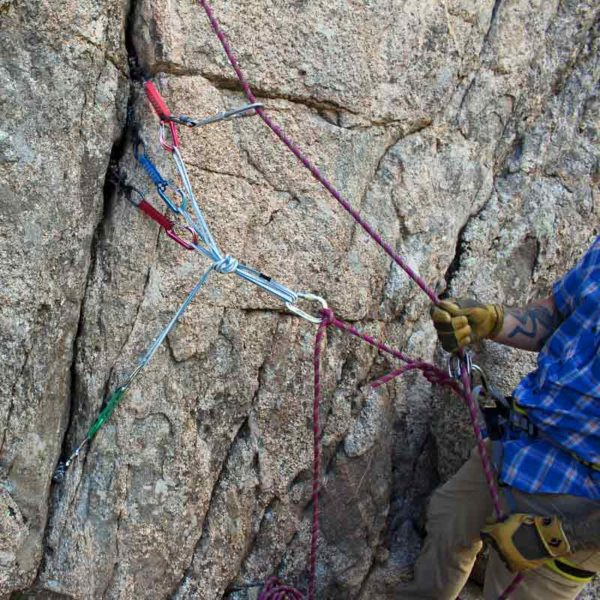 An AMGA Rock Guide demonstrates an advanced rock climbing anchor with directionals.