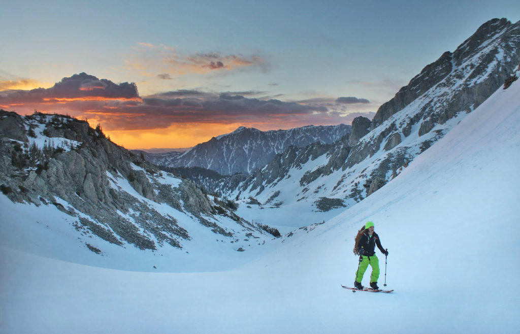 From the blog What to Pack and Wear for Backcountry Skiing, A backcountry skier skins up to Capitol Peak on a spring morning in Colorado.