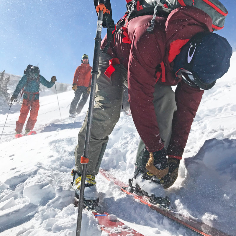 A backcountry skier buckles up their Scarpa ski boots on a day of spring skiing in Colorado from from the What to Pack and Wear for Backcountry Skiing blog
