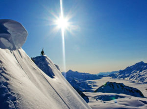 Colorado Mountain School Guide, Adam Fisher, traverses a snowy ridge with skis on his back.