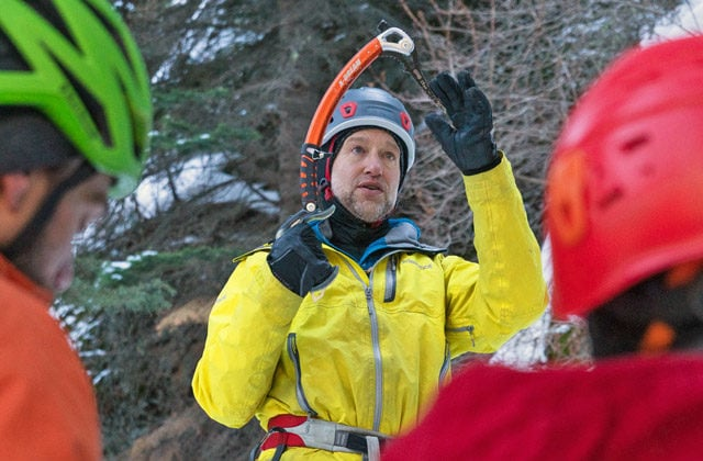 An mountaineering instructor teaches students about ice climbing tools during a class in Rocky Mountain National Park.