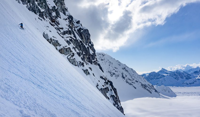 A backcountry skier looks down mountain as they carve corn snow on a spring day in Alaska.