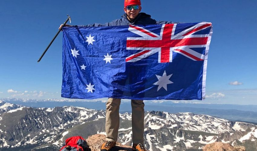 A mountaineer waves a flag on the summit of Longs Peak after having climbed The Keyhole. Longs Peak is the tallest mountain in Rocky Mountain National Park.